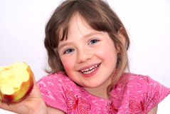 The girl. The child eat an apple. The girl is cheerful and happy. Isolated on white Stock Image
