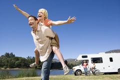Free Girl (9-11) On Father`s Back, Mother And Brother (10-12) By Motor Home In Background, Low Angle View Royalty Free Stock Photo - 41710205