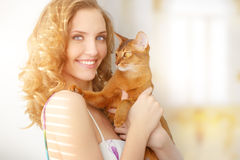 Girl with Abyssinian cat. On light background royalty free stock image