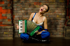 The girl with an accordion. The girl with accordion near a brick wall sings songs stock photography