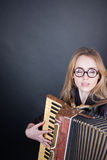 Girl with accordion and glasses Stock Image