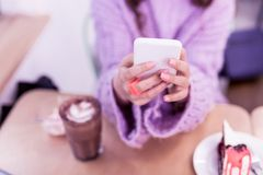 Girl with accurate pink manicure typing messages on smartphone. Chocolate cake nearby. Girl with accurate pink manicure typing messages on smartphone while being stock photos