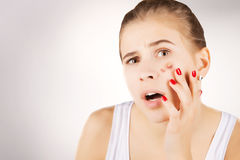 Girl with acne, grey gradient background. Girl with funny disgusted face examines her pimples royalty free stock photography