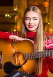 Girl with acoustic guitar in festive environment royalty free stock image