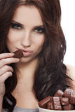 Girl in act to eat a chocolate Royalty Free Stock Photo