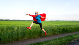 Girl acting like a super hero. In motion stock photo