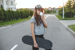 The girl with an active lifestyle starts morning  coffee and skate. Stock Photo