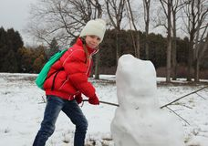 Girl actively sculpts snowman Royalty Free Stock Photo