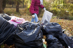 Girl activist raises trash in park. Cares about the environment Stock Photography