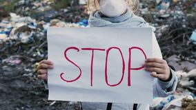 Girl activist with Stop poster on waste dump. Static outdoors shot stock footage