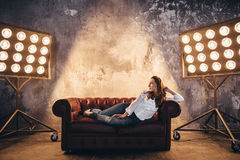 Girl actress on the couch in the light of soffits Royalty Free Stock Photo