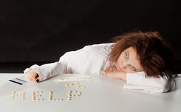 Girl addict. Addict girl at the table with the pills was the inscription of these royalty free stock photo