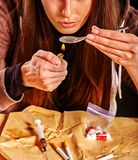 Girl addict with heroin spoon and lighter. Stock Photos
