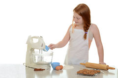 Girl adding flour to stand mixer Stock Images