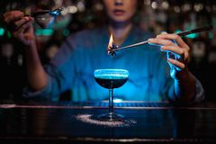 Girl adding to a brown cocktail a flamed badian with tweezers in the blue light. Girl adding to a brown cocktail a flamed badian with tweezers on the bar counter royalty free stock image