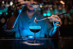 Girl adding to a brown cocktail and pour on a flamed badian on tweezers a powdered sugar in the blue light. Girl adding to a brown cocktail and pour on a flamed stock photography