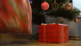 Girl adds gifts under the Christmas tree stock footage