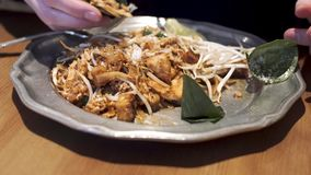Girl adds peanuts to the Pad Thai - famous Thai dish.
