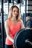 Girl adds weight to the bar royalty free stock images