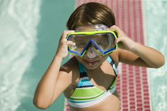 Girl (7-9) Adjusting Goggles in swimming pool portrait. Stock Photo