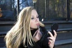 Girl adjusting her makeup Stock Images
