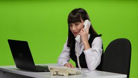 Girl administrator answers the phone call and makes notes. Studio stock video