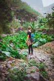 Girl admire the lotus plants on her way in lush green valley of the mountains. Santo Antao. Cape Verde royalty free stock image