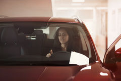 Girl admires interior of car Royalty Free Stock Photo