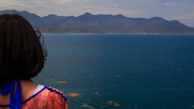 Girl admires scenery of seascape turns to camera against sea stock video