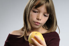 Girl admiring apple Royalty Free Stock Image