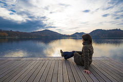 Girl admiring lake. Girl admiring panorama on the dock of the lake, Ivrea Italy Stock Images