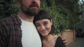 Girl adores her boyfriend. Happy attractive couple of young millennials or contemporary hipster newlyweds stand outdoors on street, wear fashionable trendy stock video