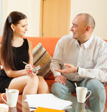 Girl with  adult man discussing documents Stock Photos