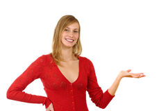 Girl with advertise gesture. Smiling blonde young girl in red with advertise gesture on white background Royalty Free Stock Photos