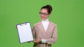 Girl advertising agent shows important information on the tablet. Green screen. Slow motion. Girl advertising agent shows important information on the tablet stock footage