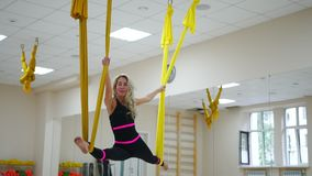 The girl at the Aero yoga classes is in the twine sitting on a hammock in the air.  stock video