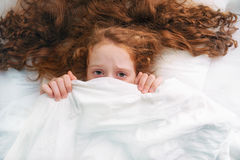 Girl afraid sleeping and pulling quilt on head. Sad little girl afraid sleeping and pulling quilt on head royalty free stock photography