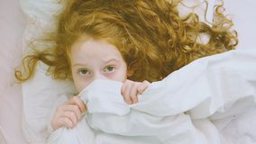 Girl afraid sleeping and pulling quilt on head. stock footage