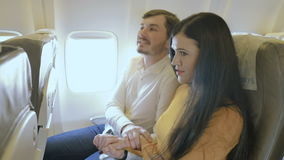 The girl is afraid to fly in the plane and the guy calms her down. Pretty girl and handsome guy are sitting on the passenger`s seats in the plane. Bearded man stock video footage