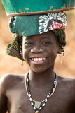 Girl in Africa. Smiling young girl in Africa carrying water in a bucket on her head Royalty Free Stock Photography