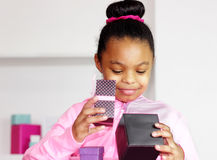 She receives a nice gift. Girl of African American - Hispanic descent smiles upon looking inside box with a present Stock Photography