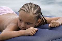Girl with the African pigtails lies in water Royalty Free Stock Photography