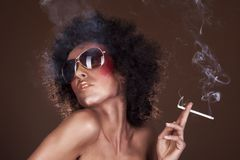 Girl with afro hair and a cigarette Stock Photo