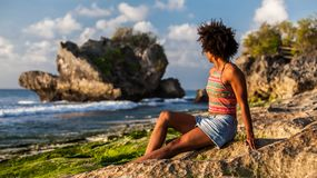 Girl with afro hairstyle at Padang Padang beach. Melanesian pacific islander athlete girl with afro hairstyle at Padang Padang beach, Bali, Indonesia at sunset Royalty Free Stock Photo