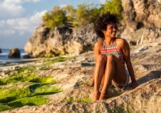 Girl with afro hairstyle at Padang Padang beach. Melanesian pacific islander athlete girl with afro hairstyle at Padang Padang beach, Bali, Indonesia at sunset Royalty Free Stock Photography
