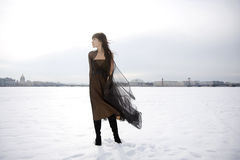 Girl against a background of snow and the city. Royalty Free Stock Images