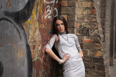 Girl against brick wall Stock Images