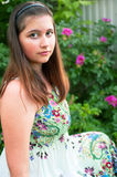Girl against bush of dogrose Royalty Free Stock Photography