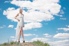 The girl against clouds. The blonde in a white dress against the sky Royalty Free Stock Images