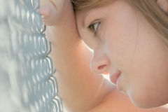 Girl against fence. Pretty teen girl with wishful look, leaning against chain link fence. backlit, shallow dof Royalty Free Stock Image